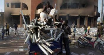 People load goods looted from a building, which according to locals, belongs to Francois Compaore, the younger brother of Burkina Faso's President Blaise Compaore, in Ouagadougou